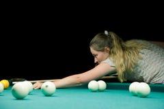 Woman aiming for billiard table Stock Photos