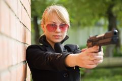 Woman aiming black gun Royalty Free Stock Image