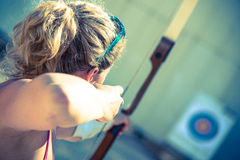 Woman aiming with a bow. Young woman aiming with a bow Royalty Free Stock Image