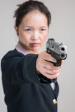 Woman aiming a hand gun Stock Images