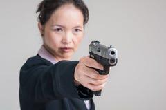 Woman aiming a hand gun Royalty Free Stock Image
