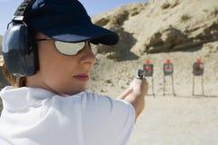 Woman Aiming Hand Gun At Firing Range. Closeup of a women aiming hand gun at firing range in desert Stock Images
