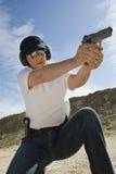 Woman Aiming Hand Gun At Firing Range. Female officer aiming hand gun at firing range in desert Royalty Free Stock Images