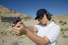 Woman Aiming Hand Gun At Firing Range In Desert Royalty Free Stock Photography