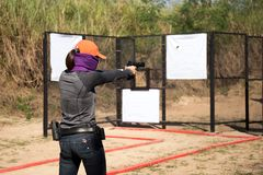 Woman aiming pistol in shooting range. For competition royalty free stock photography