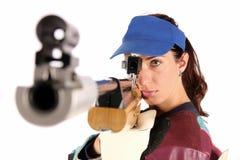 Woman aiming a pneumatic air rifle. Beautiful young woman aiming a pneumatic air rifle royalty free stock images