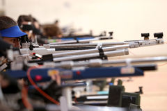 Woman aiming a pneumatic air rifle on sports competition. Young woman aiming a pneumatic air rifle on sports competition royalty free stock image