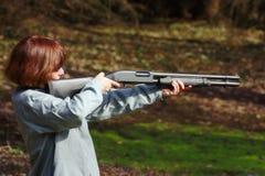 Woman aiming a shotgun. A white female aiming a 12 gauge shotgun Royalty Free Stock Images