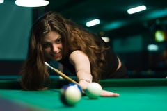 Woman aiming to the billiard ball Stock Image
