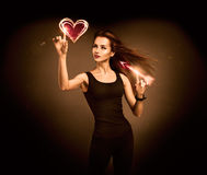 Woman Aiming to the Glowing Heart with an Arrow Royalty Free Stock Photo