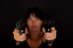 Woman aiming two guns Stock Photography