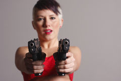 Woman aiming two pistols Stock Photography