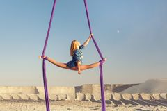 Woman aerial acrobat on canvases. Woman is an air acrobat on canvases, in the desert high above the earth Royalty Free Stock Photography