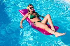 Woman on air mattress in swimming pool water Royalty Free Stock Image