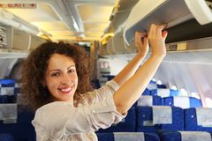 Woman on airplane adds baggage. Young beautiful woman on airplane adds baggage, rows of blue seats Stock Image