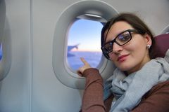Woman in airplane travel. Happy young tourist woman is sitting in the airplane looking window and travel to summer vacation stock image
