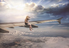 Woman on airplane wing. A woman sits casually on a plane wing high in the sky Stock Photo