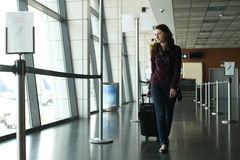 Woman in the airport. Casual woman with a roller luggage walking in the airport departure gate stock photos
