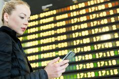 Woman at airport in front of flight information board checking her phone. Young woman at international airport looking at the flight information board, holding Stock Images
