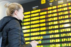 Woman at airport in front of flight information board checking her phone. Young woman at international airport looking at the flight information board, holding Royalty Free Stock Photos