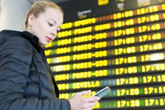 Woman at airport in front of flight information board checking her phone. Young woman at international airport looking at the flight information board, holding Stock Image