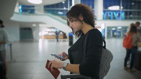 Woman at the airport holding the passport and thinking about the trip stock video