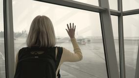 Woman at the airport looking at the plane stock video