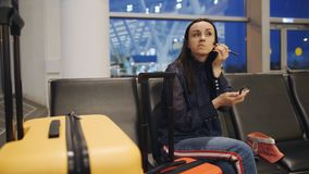 The woman in the airport lounge doing her makeup, waiting for the start of registration. stock video footage