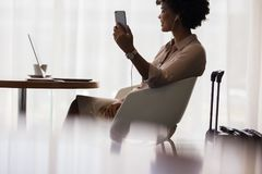 Woman at airport lounge making video call. Happy woman making video call from mobile phone while sitting at airport lounge. Business woman waiting for flight at royalty free stock photos