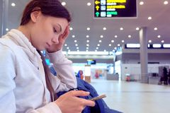 Woman at the airport with a mobile phone in her hands waiting for her flight, side view. stock images