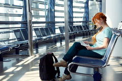 Woman at the airport. Redhead girl with tablet computer. business and travel Stock Images
