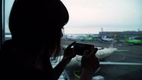 Woman in airport terminal awaiting flight takes pictures on a smartphone.  stock video