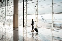 Woman at the airport. View on the aiport window with woman walking with suitcase at the departure hall of the airport. Wide angle view with copy space stock photo