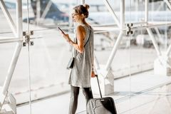 Woman at the airport. Young woman standing with phone near the airport window waiting for the flight stock image