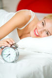 Woman with alarm clock on bed Royalty Free Stock Image