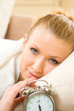 Woman with alarm-clock on bed Royalty Free Stock Photography