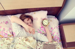 Woman and alarm clock in bedroom Stock Images