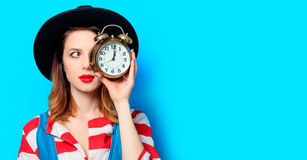 Woman with alarm clock. Portrait of young suprised red-haired white european woman in hat and red striped shirt with alarm clock on blue background Royalty Free Stock Photography