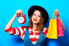 Woman with alarm clock and shopping bags Stock Photography