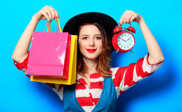 Woman with alarm clock and shopping bags Stock Photo