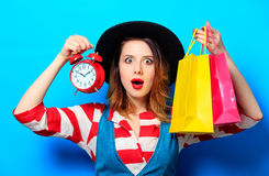 Woman with alarm clock and shopping bags Royalty Free Stock Photo