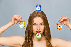 Woman with alarm clocks on grey background Royalty Free Stock Image