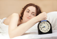 Woman and an alarm (focus on alarm) Royalty Free Stock Photo