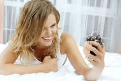 Woman with alarmclock on the bed. Stock Image