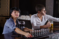 Woman alcoholic lining up a row of drinks. Woman alcoholic sitting at a bar counter carefully lining up a row of drinks in shot glasses as she prepares to down Royalty Free Stock Image