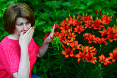 woman with an allergic rhinitis near lilies in nature Stock Images