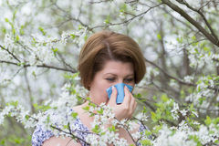 Woman with allergic rhinitis in  spring garden Stock Photography