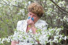 Woman with allergic rhinitis in  spring garden Royalty Free Stock Photos