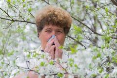 Woman with allergic rhinitis in  spring garden Stock Photo