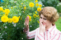 The woman is allergic to flowers Royalty Free Stock Photo